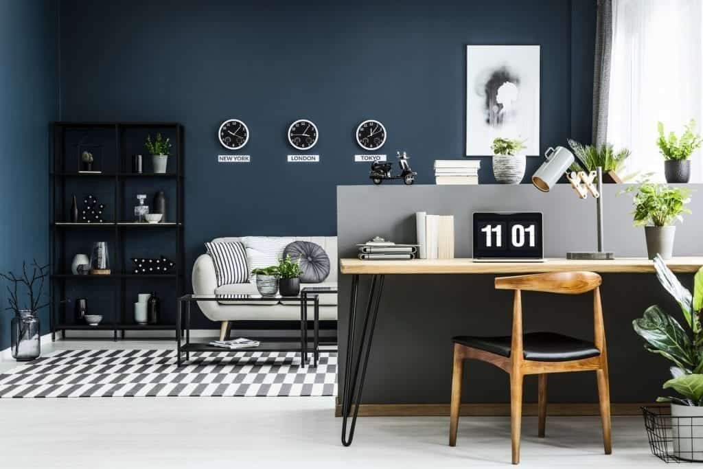 Sleek and stylish bark blue, grey and white home office set up in a studio flat