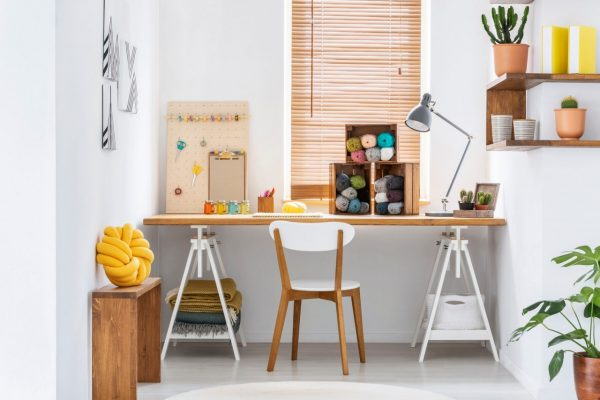 Scandinavian style hobby room interior with workspace for knitting, sewing, crocheting and designing handmade home textiles. Real photo.