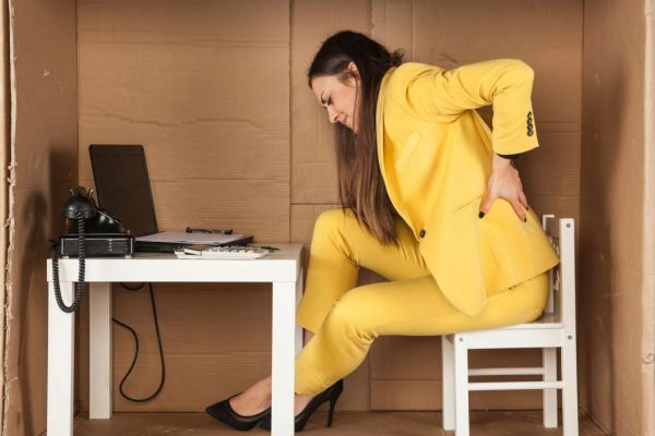 Woman with back pain sitting at a desk set up in a cardboard box